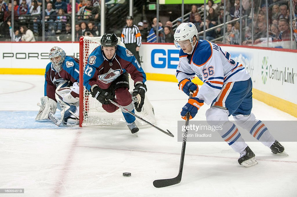 Teemu Hartikainen #56 of the Edmonton Oilers looks to put the puck in play as Semyon Varlamov #1 and Matt Hunwick #22 of the Colorado Avalanche defend during a game at the Pepsi Center on February 2, 2013 in Denver, Colorado. The Avalanche beat the Oilers 3-1.