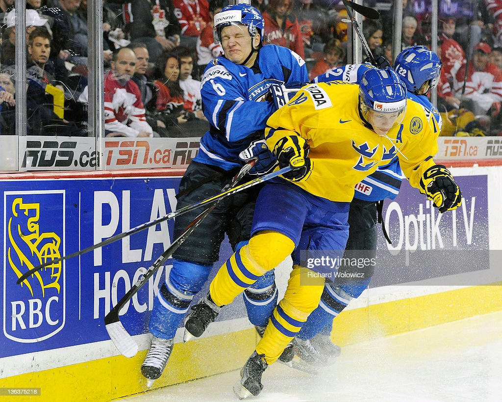 Teemu Pulkkinen and Miikka Salomaki of Team Finland body check Joakim Nordstrom of Team Sweden during the 2012 World Junior Hockey Championship...