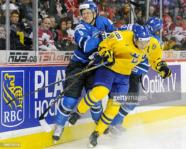 Teemu Pulkkinen and Miikka Salomaki of Team Finland body check Joakim Nordstrom of Team Sweden during the 2012 World Junior Hockey Championship...