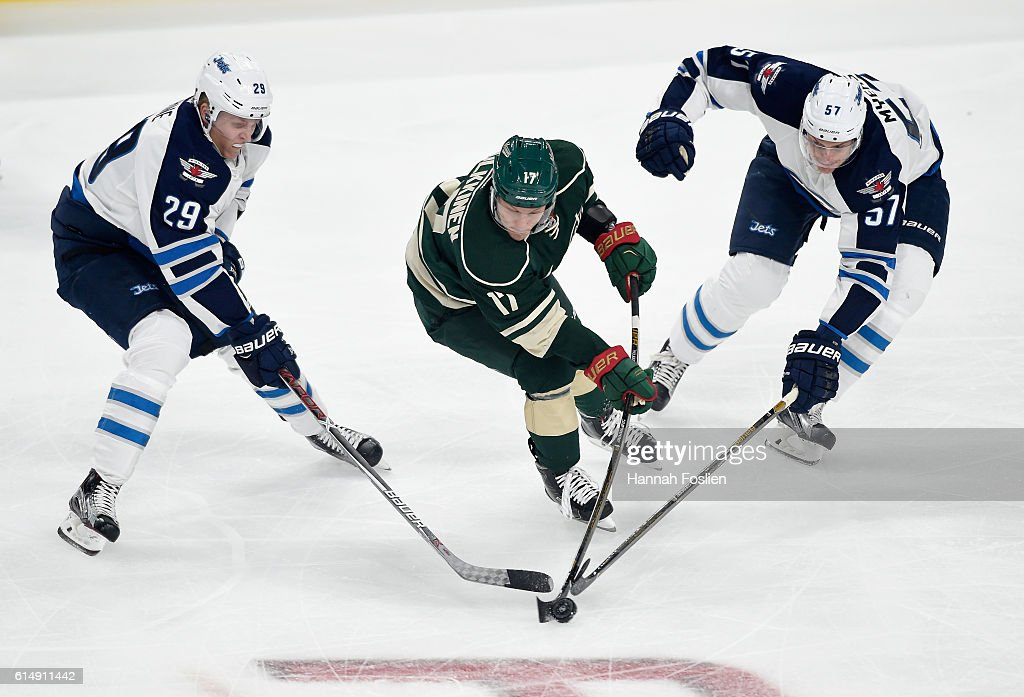 Teemu Pulkkinen #17 of the Minnesota Wild passes the puck away from Patrik Laine #29 and Tyler Myers #57 of the Winnipeg Jets during the first period of the game on October 15, 2016 at Xcel Energy Center in St Paul, Minnesota.