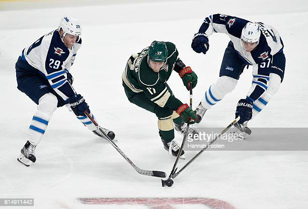 Teemu Pulkkinen of the Minnesota Wild passes the puck away from Patrik Laine and Tyler Myers of the Winnipeg Jets during the first period of the game...
