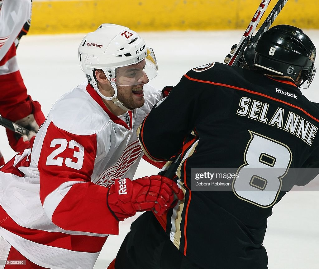 Teemu Selanne #8 is checked hard by Brian Lashoff #23 of the Detroit Red Wings which led to a fight in the 2nd period. March 22, 2013 at Honda Center in Anaheim, California.