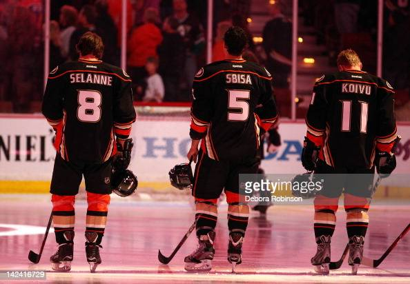 Teemu Selanne Luca Sbisa and Saku Koivu of the Anaheim Ducks stand on the ice as the National Anthem is sung before the game against the Edmonton...