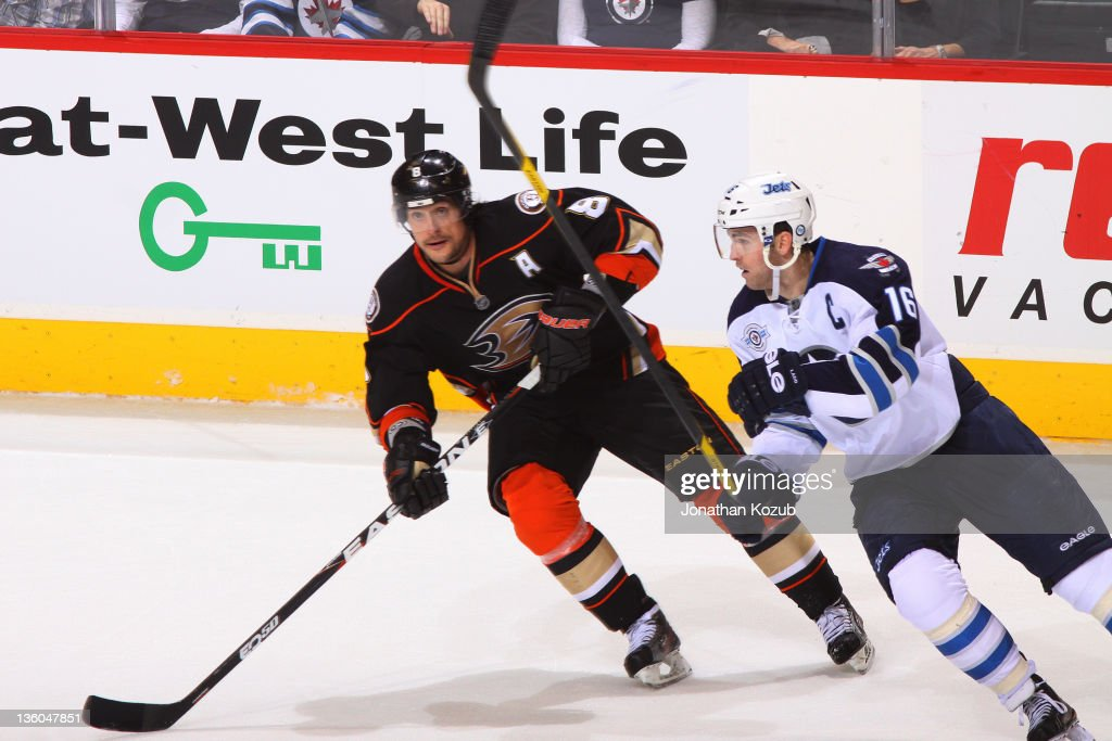 Teemu Selanne #8 of the Anaheim Ducks and <a gi-track='captionPersonalityLinkClicked' href=/galleries/search?phrase=Andrew+Ladd&family=editorial&specificpeople=228452 ng-click='$event.stopPropagation()'>Andrew Ladd</a> #16 of the Winnipeg Jets follow the play up ice during third period action at the MTS Centre on December 17, 2011 in Winnipeg, Manitoba, Canada.