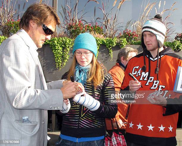 Teemu Selanne of the Anaheim Ducks autographs memorabilia for fans before heading into the arena before the game against the New York Rangers on...