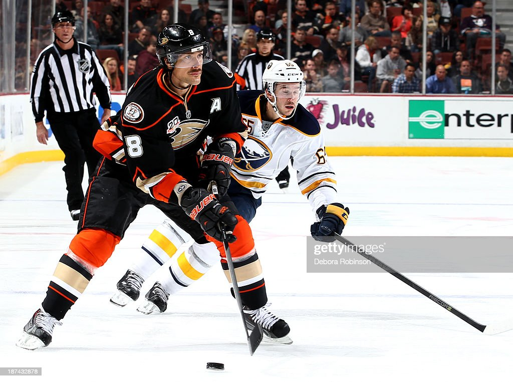 Teemu Selanne #8 of the Anaheim Ducks handles the puck against Brian Flynn #65 of the Buffalo Sabres at Honda Center on November 8, 2013 in Anaheim, California.