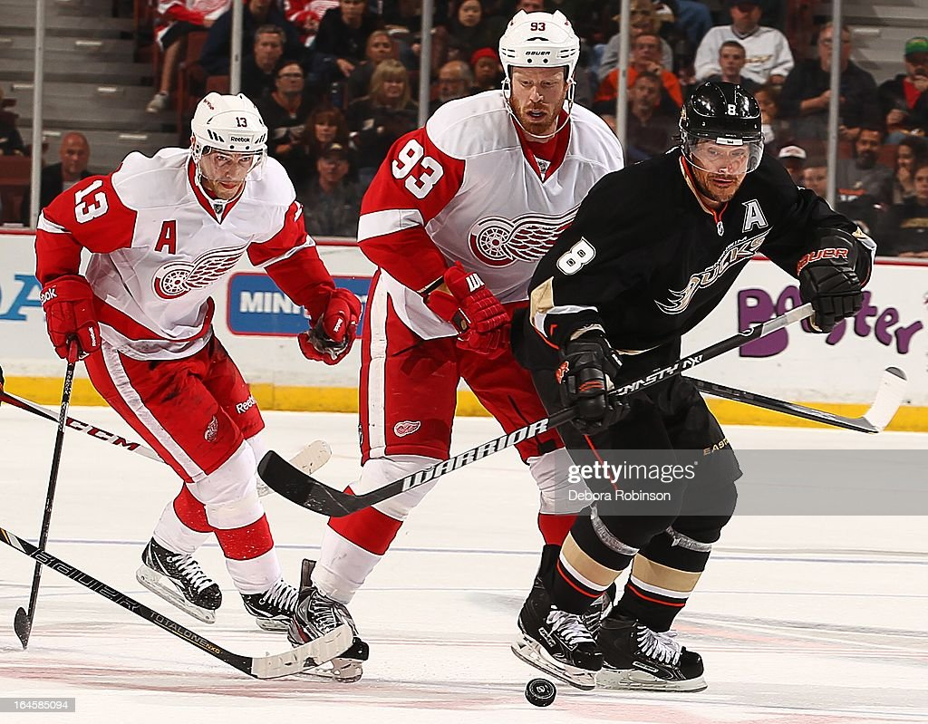 Teemu Selanne #8 of the Anaheim Ducks moves the puck past Detroit Red Wings players <a gi-track='captionPersonalityLinkClicked' href=/galleries/search?phrase=Pavel+Datsyuk&family=editorial&specificpeople=202893 ng-click='$event.stopPropagation()'>Pavel Datsyuk</a> #13 and <a gi-track='captionPersonalityLinkClicked' href=/galleries/search?phrase=Johan+Franzen&family=editorial&specificpeople=624356 ng-click='$event.stopPropagation()'>Johan Franzen</a> #93 at center ice. Selanne ties Teppo Numminen as leader in all time games played by a Finnish born player on March 24, 2013 at Honda Center in Anaheim, California.