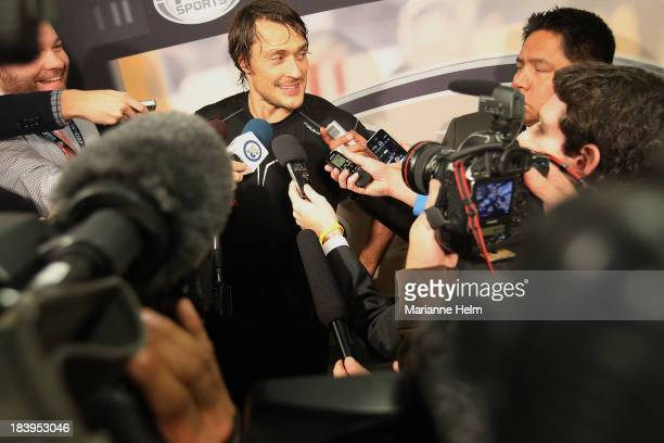 Teemu Selanne of the Anaheim Ducks speaks with the media during a press scrum after an NHL game against the Winnipeg Jets at the MTS Centre on...