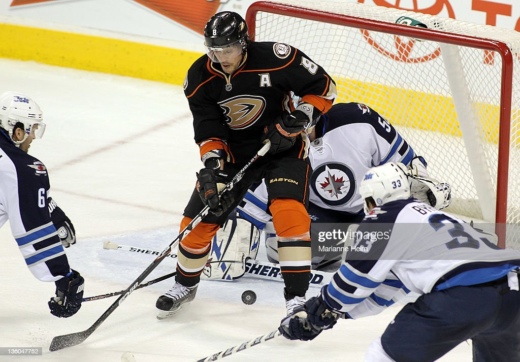 Teemu Selanne #8 of the Anaheim Ducks tries to get control on the puck in front of the Winnipeg Jets net in NHL action at the MTS Centre on December 17, 2011 in Winnipeg, Manitoba, Canada.