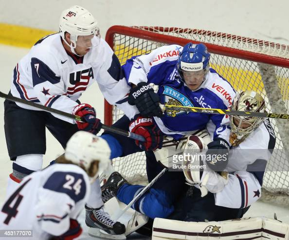 Teemu Turunen of Team Finland goes in on Thatcher Demko and JT Compher of USA White during the 2014 USA Hockey Junior Evaluation Campat Lake Placid...