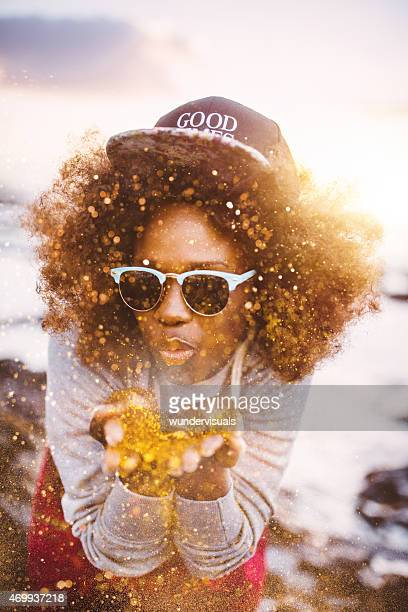 Teen Afro hipster blowing gold glitter from her hands