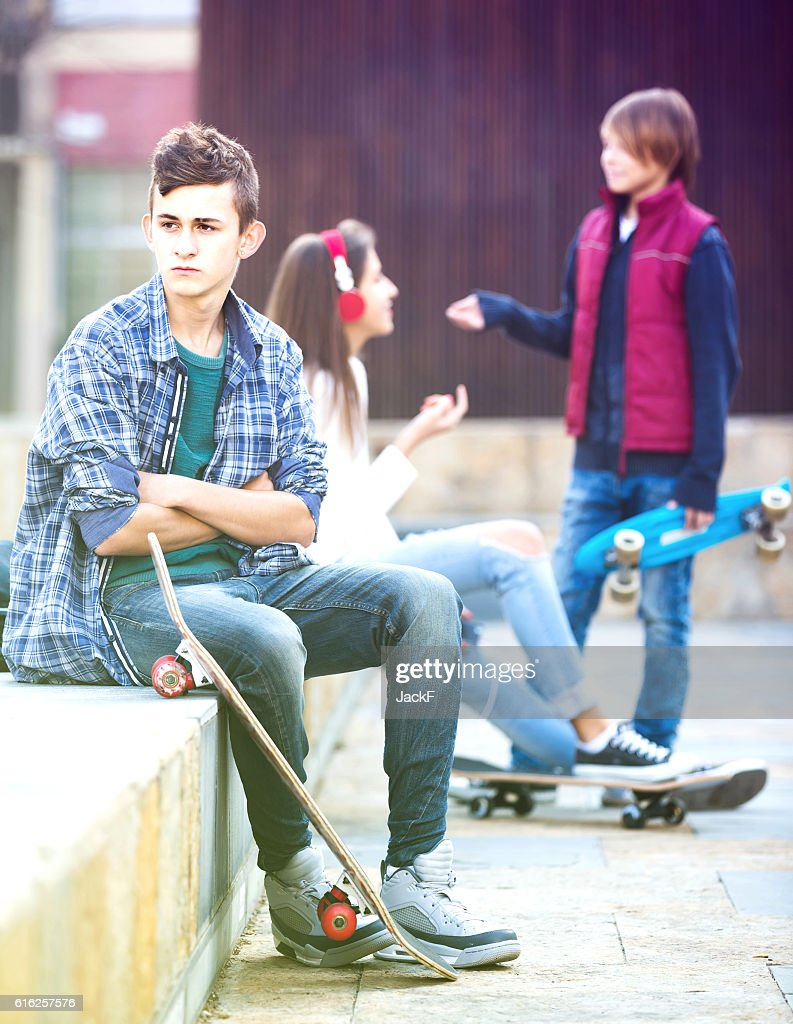 teen and his friends after conflict outdoors : Stock Photo