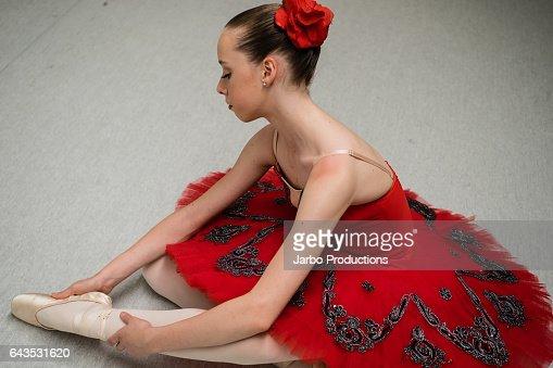 Teen Ballerina poses on studio floor