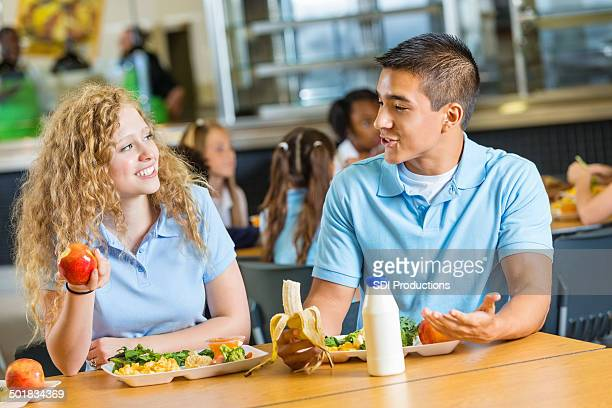 Teen boy and girl having lunch together in school cafeteria