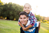 A teen boy carrying his younger brother on the back and smiling at the camera in a horizontal waist up shot outdoors.