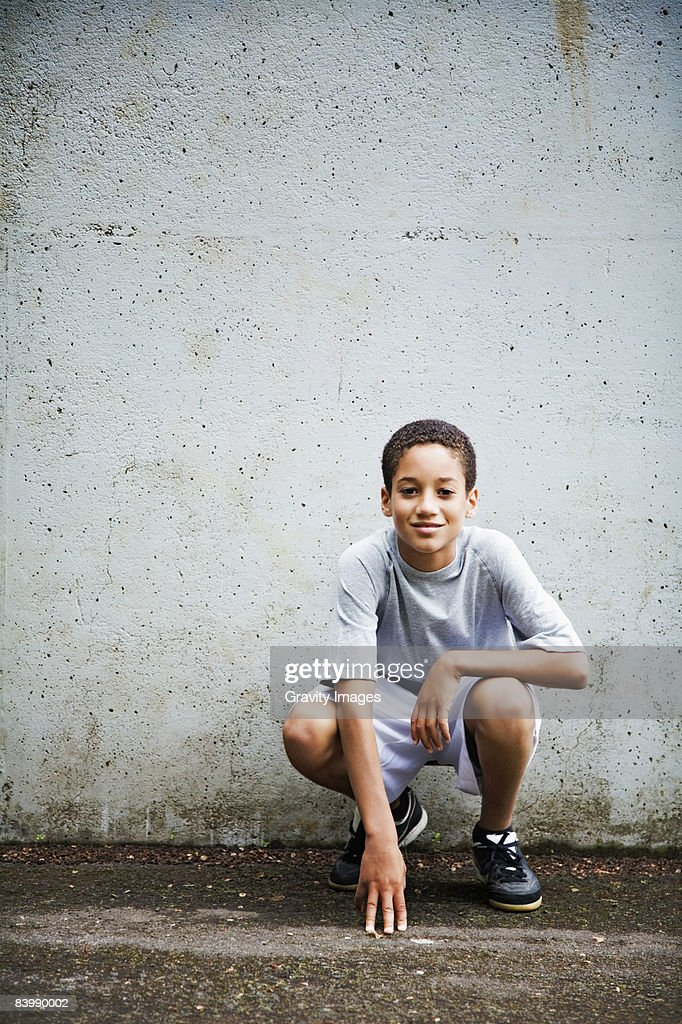 Teen Boy Crouched Against a Wall : Stock Photo