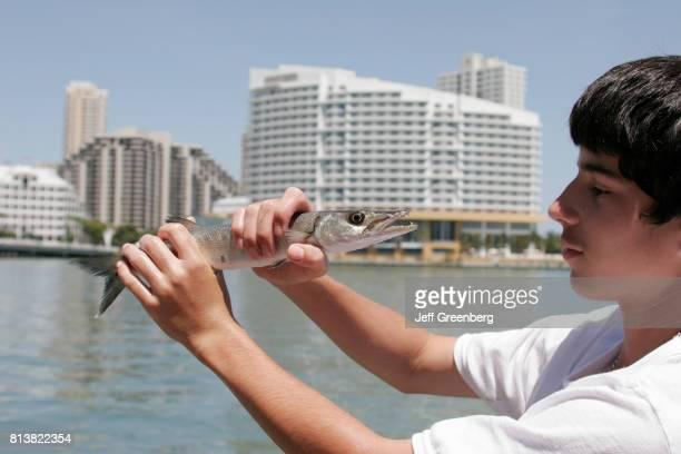 A teen boy holding a barracuda fish