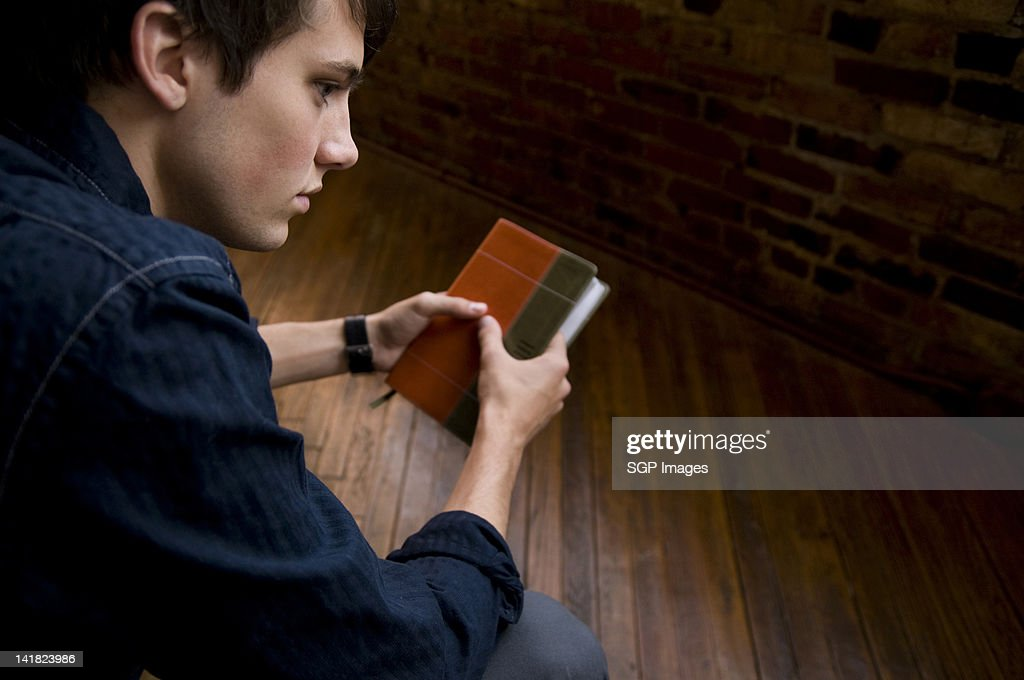 Teen boy holding bible book : Stock Photo