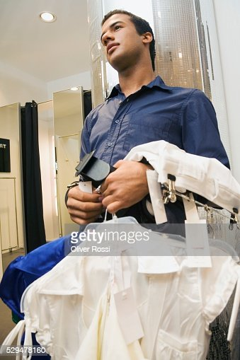 Teen boy holding clothing on hangers in store : Stock Photo
