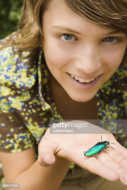 Teen boy holding insect