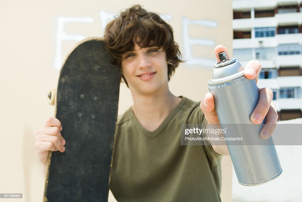 Teen boy holding spray paint can, smiling at camera