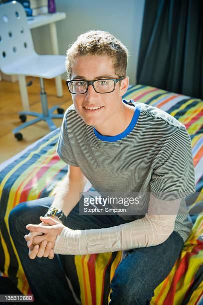 teen boy in his bedroom with broken arm