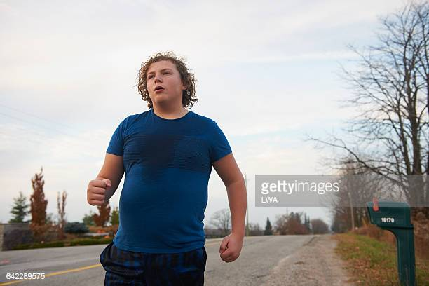 Teen boy jogging on country road