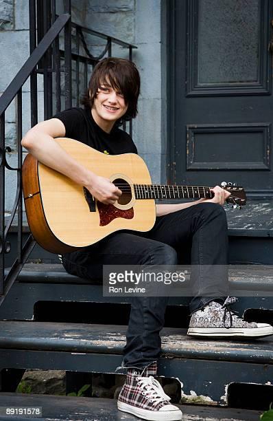 Teen boy playing guitar on porch