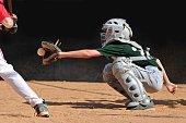 Little league baseball player catches a strike.