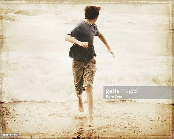 Teen Boy Running at Ocean- Retro Toned with Grunge Texture