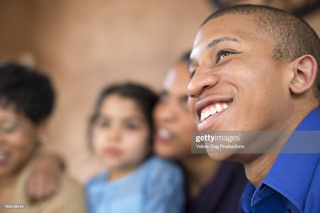 Teen boy Smiling, family in background : Stock Photo