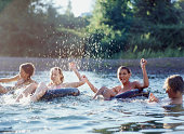 Teen boy splashing teen girls (14-16) floating on inner tubes