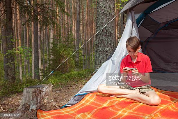 Teen boy using phone in a summer forest