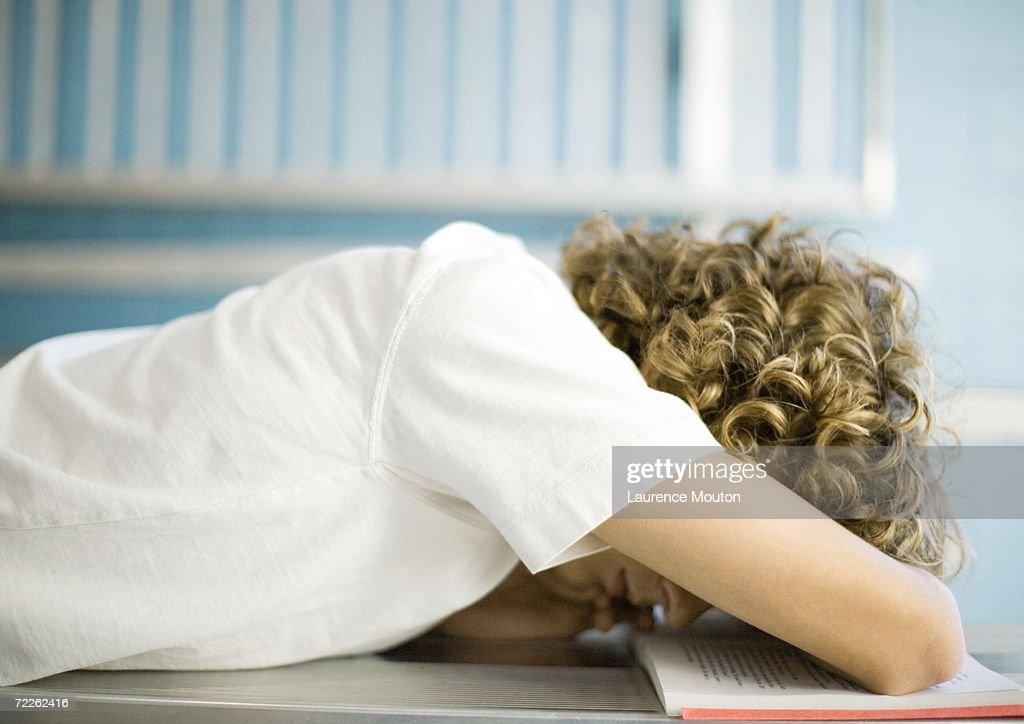 Teen boy with head down on school book