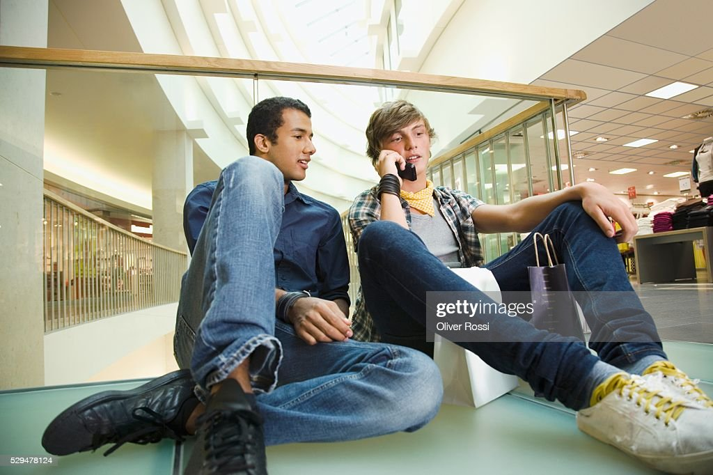 Teen boys using cell phone in department store : Stock Photo