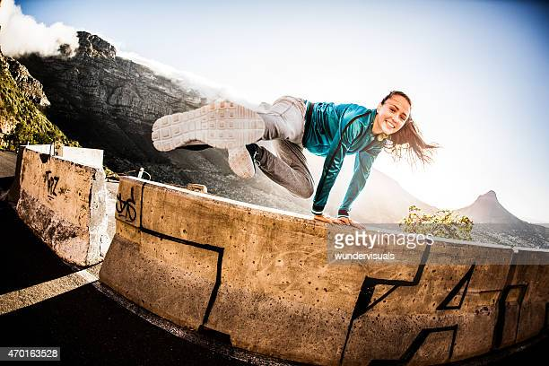 Teen breakdancing girl doing a parkour jump over a wall