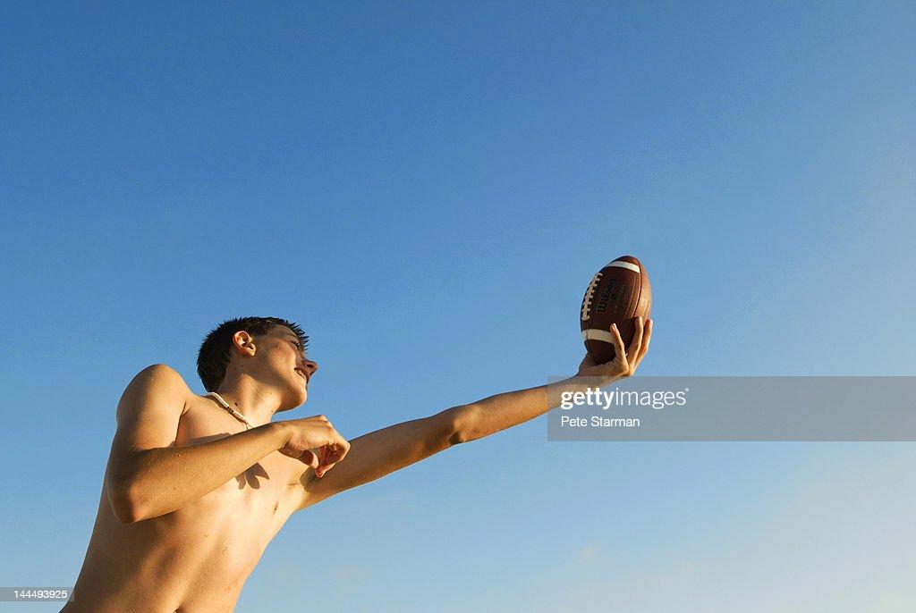 Teen catching football on a beach : Stock Photo