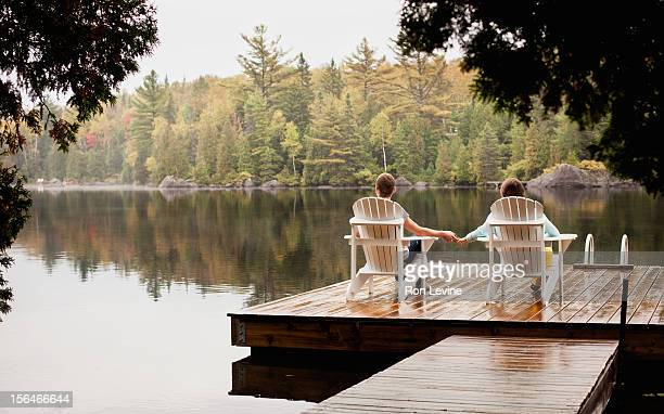 Teen couple holding hands by a lake