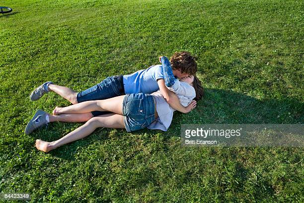 Teen couple laying on grass, kissing