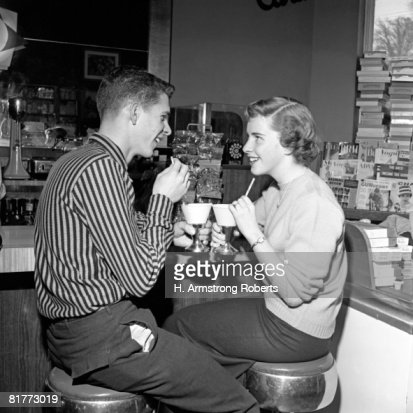 Teen Couple On Stools At Soda Fountain Drinking Shakes & Smiling At Each Other. : Stock Photo