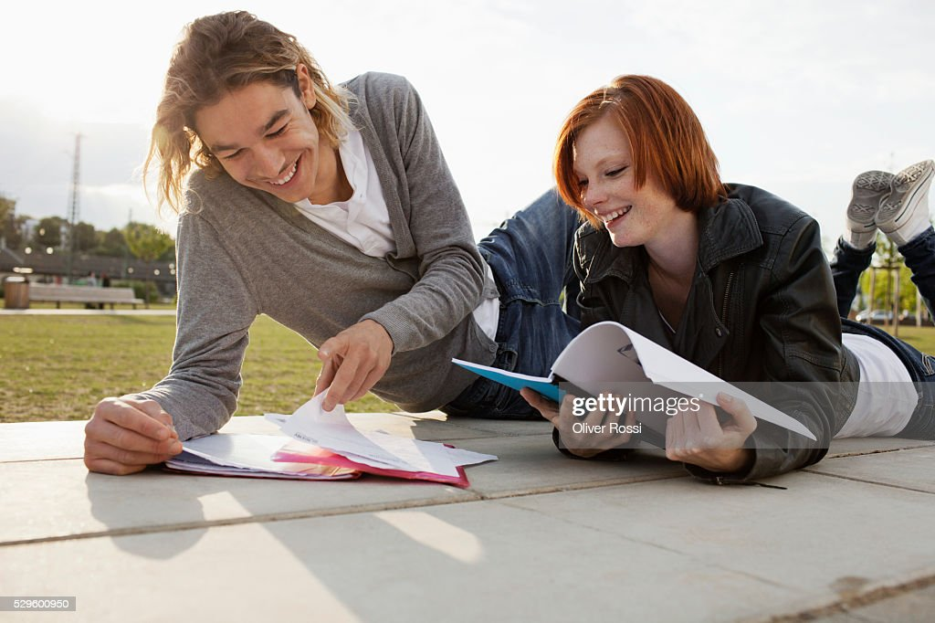 Teen (16-17) couple reading textbooks in park : Foto de stock
