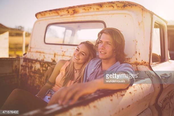 Teen paar sitzen zusammen in einem liebevoll vintage-truck