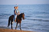 Teen couple together on horseback along beach