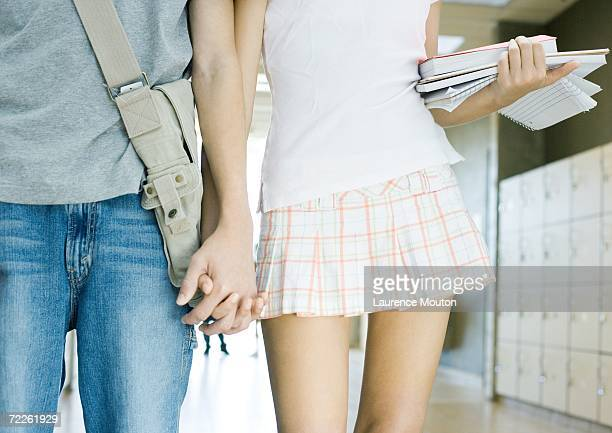 Teen couple walking in school hallway, mid section