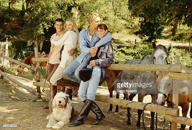 Teen couples (17-19) leaning on fence in horse farm