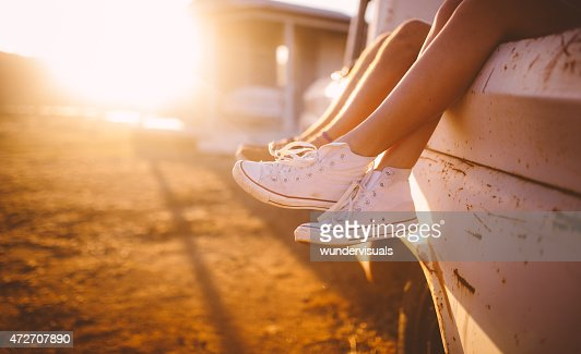 Teen couple's legs hanging out of vehicle with sun flare