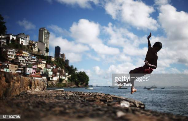 A teen dives off the rocks in front of the Gamboa de Baixo community on April 18 2015 in Salvador Brazil