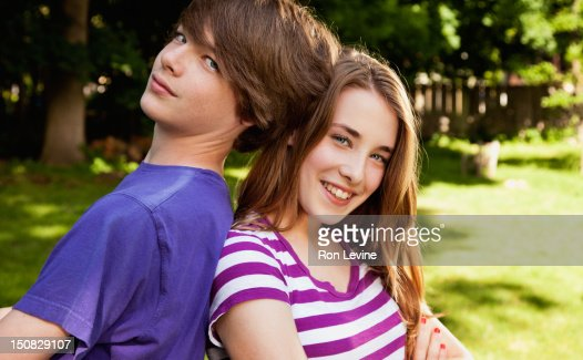 Teen Fraternal Twins Leaning On Each Other Stock Photo