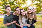 Teen group of friends together at park after school, taking a selfie and having fun. Lifestyle and friendship concepts