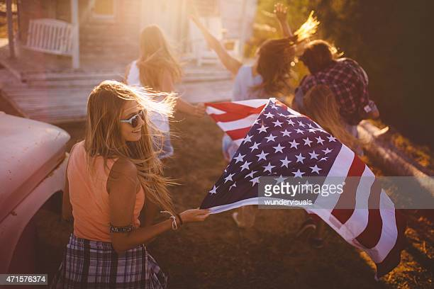 Teen friends carrying an American flag outside